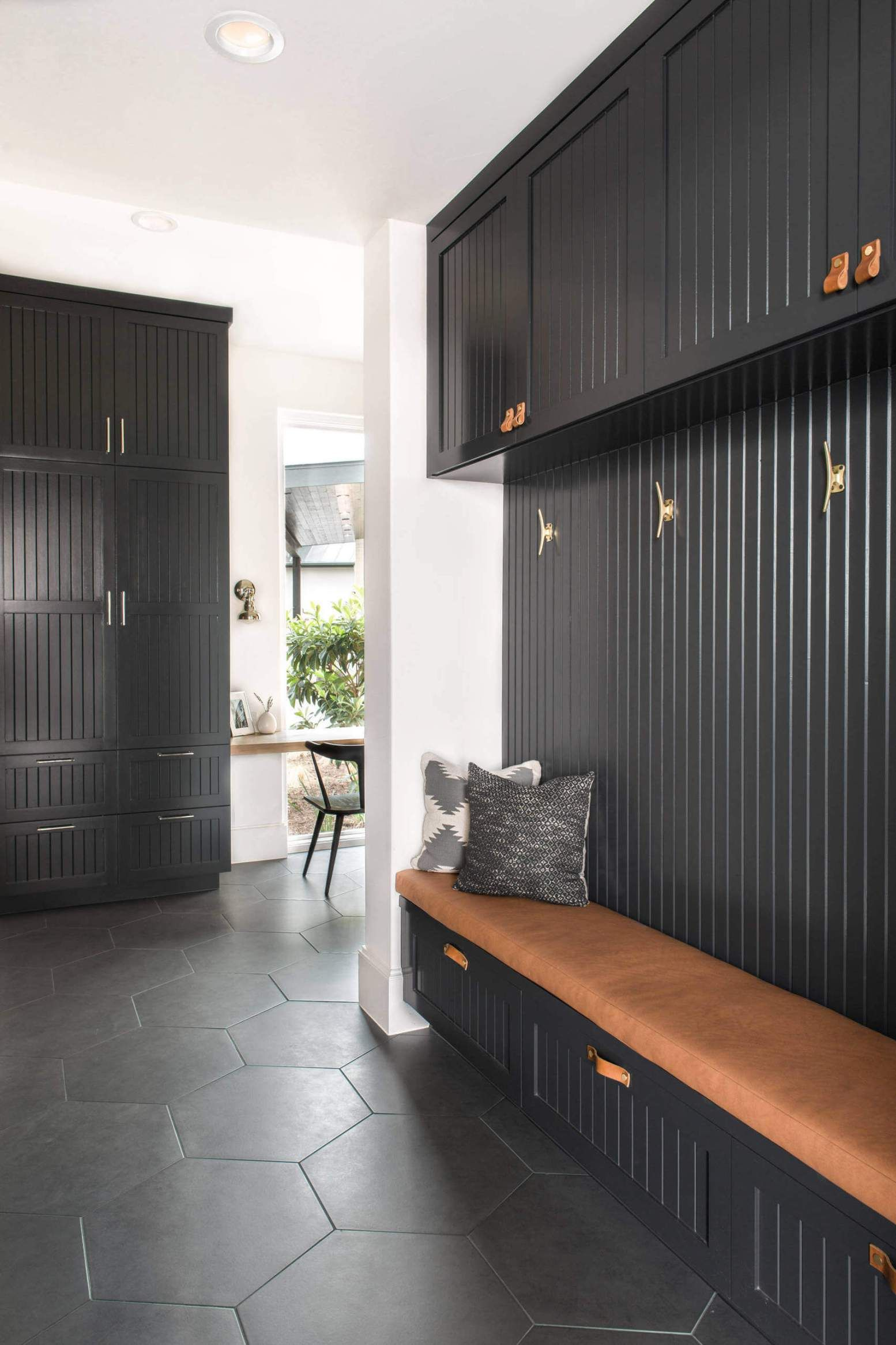 black entrance, black hexagonal floor tiles, black wooden cabinet, long brown cushion
