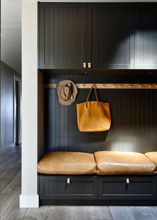 black entrance, black wooden wall, black wooden cabinet, brown hook rod, brown leather cushion
