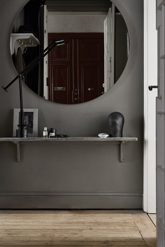 black entrance, grey wall, round mirror, floating shelves