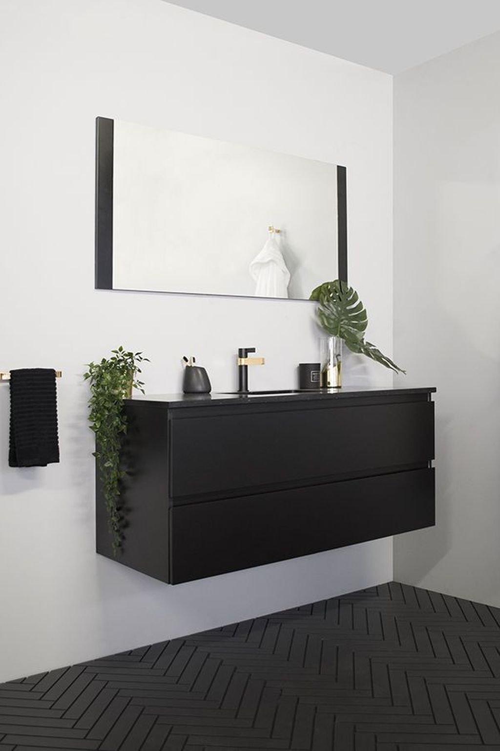 black floating cabinet, black patterned floor, white wall, black framed mirror