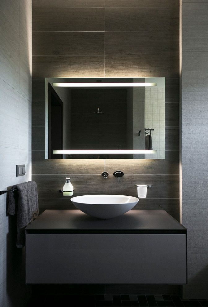 black vanity, black floating cabinet, white round sink, black accent wall, mirror, white wall