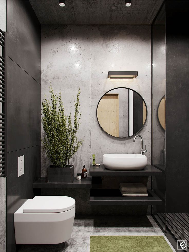 black vanity, white accent wall, black shelves, round mirror, white sink, grey floor, white toilet