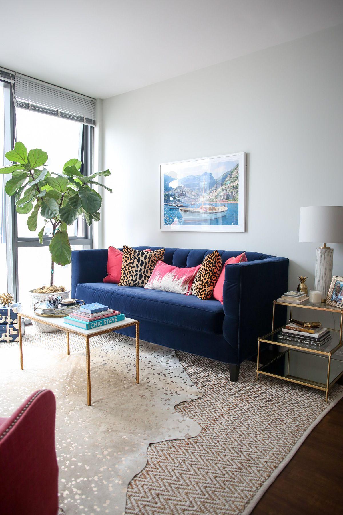 blue velvet sofa in living room, white wall, wooden floor, brown rug, glass side table with golden lines, glass coffee table with golden lines