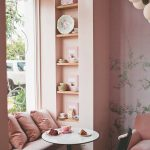 Breakfast Nook, Wooden Floor, Pink Wall, Pink Wallpaper, Pink Shelves, White Bench, Pink Pillows, White Round Tables, Black Chair