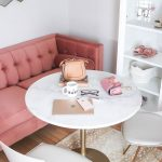 Breakfast Nook, Wooden Floor, White Round Table, White Chairs With Golden Legs, White Shelves, Pink Tufted Sofa