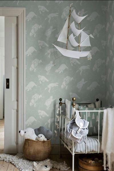 child bedroom, wooden floor, blue wallpaper, white ironed crib, white paper boat