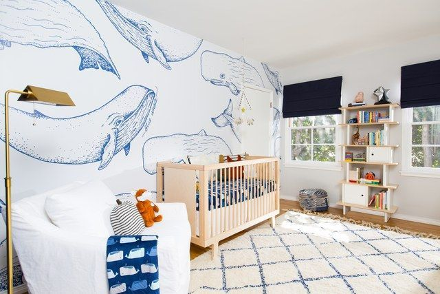 child bedroom, wooden floor, white patterned rug, wooden crib, white chair white wooden shelves