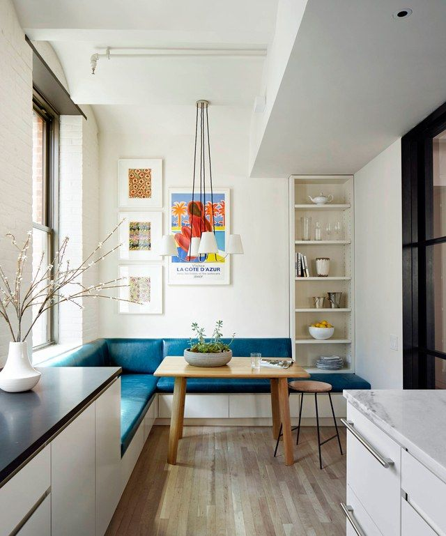 dining nook, wooden floor, white bench with blue cushion, wooden table, wooden brown leather stool, white traditional pendant, indented helves, white kitchen cabinet,