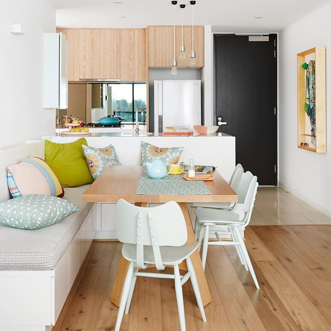 dining nook, wooden floor, white wall, white built in bench, wooden table, white chairs, white kitchen island, wooden cabinet