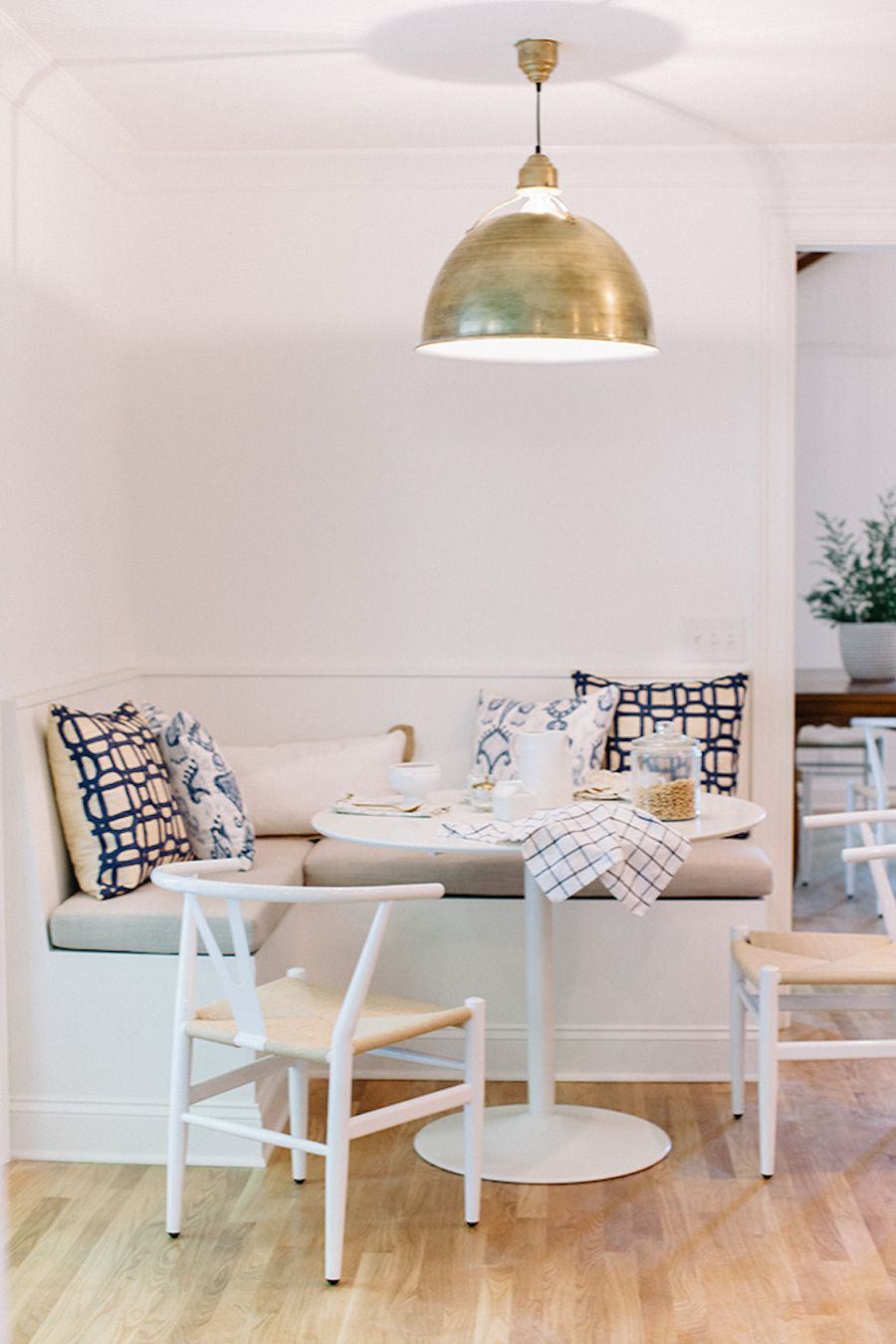 dining nook, wooden floor, white wall, white round table, white bench, grey cushion, white chairs