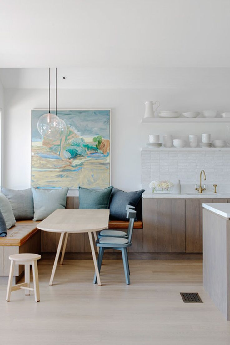 dining nook, wooden floor, white wall, wooden bench, wooden cabinet, white counter top, wooden table, blue chairs, wooden stool, white floating shelves, round glass pendant