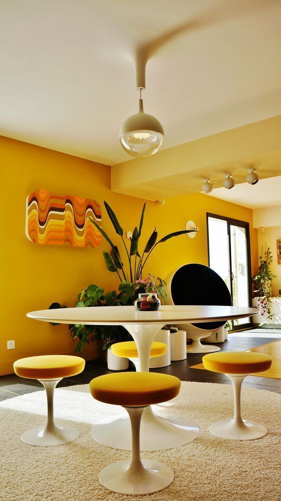 dining room, black floor, yellow wall, wooden round table, yellow stools, brown round rug, glass pendant