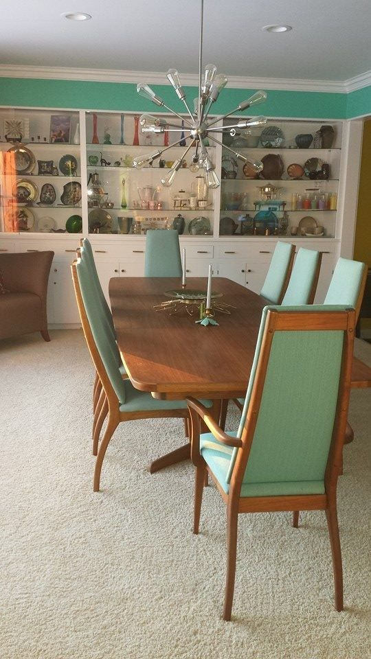 dining room, grey rug, wooden chairs with green cushion, white cupboard, wooden table
