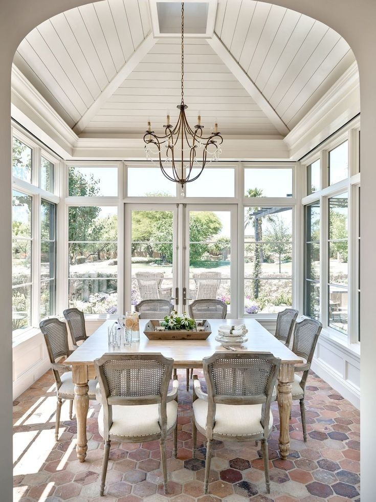 dining room, hexagonal brick floor, white wooden vaulted ceiling, wooden table, grey wooden chairs, chandelier