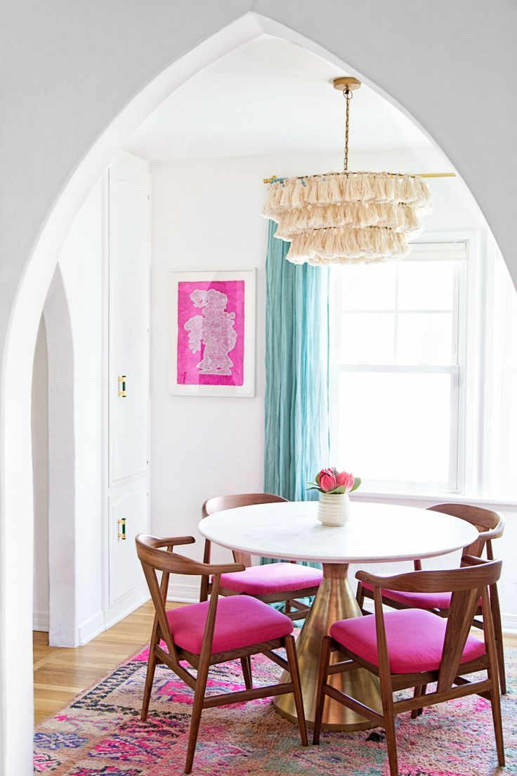 dining room, wooden floor, pink patterned rug, white round table, wooden chairs with pink cushion, white wall, fringed lighting fixture