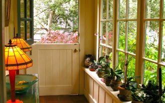 entrance, orange brown floor tiles, white wooden window bay, white wooden wall, glass window, white wooden half door, wooden door