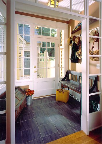 entryway, grey floor, cream wall, white framed door, bench, chest