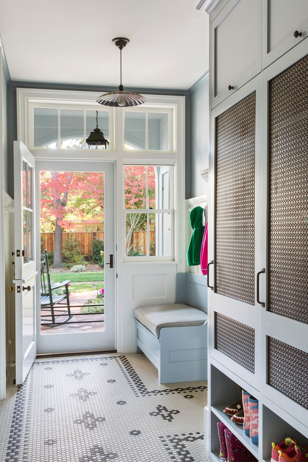entryway, tiny hexagonal floor tiles, white wall, light blue bench, white framed door and window, cabinet