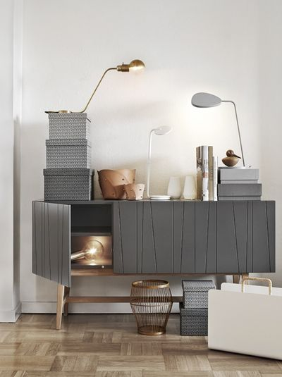 grey cabinet with lines, white wall, brown floor, table lamp