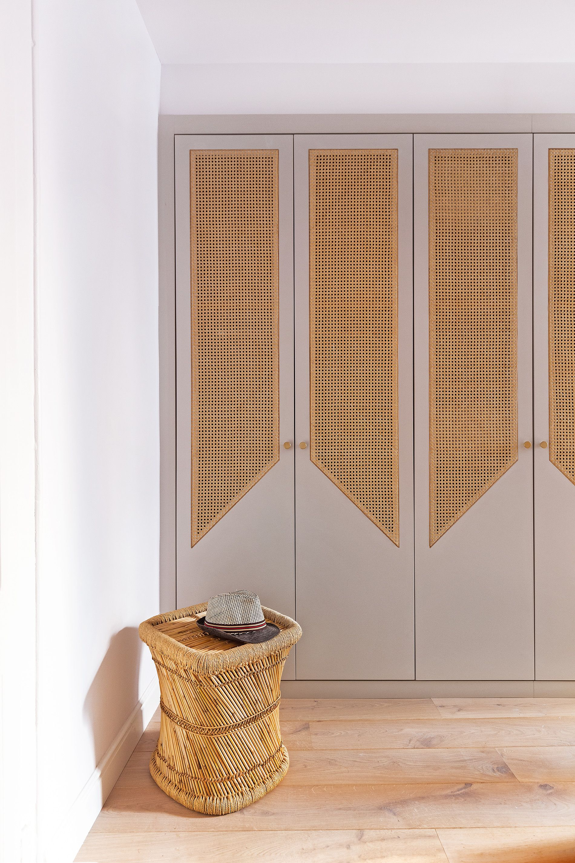 grey cupboard, rattan accent, wooden floor, rattan ottoman, white wall