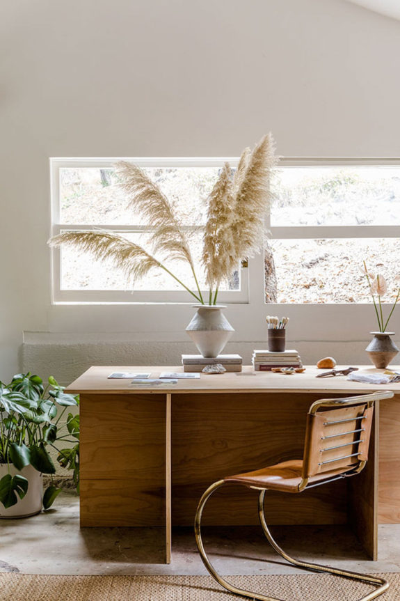 home office, concrete floor, wooden table, curvy office chair with leather seat, white wall, plants