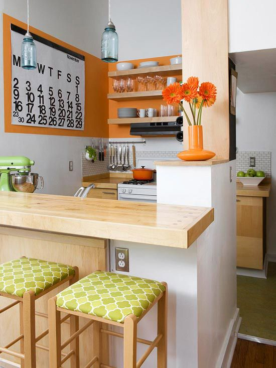kitchen, brown floor, white wall, orange wall, wooden counter top, wooden island bar, green stools, open shelves