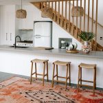 Kitchen, Grey Floor, White Wooden Island, Grey Top, Wooden Wall, Wooden Stairs, Rattan Pendant, Wooden Stools