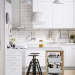 Kitchen, Grey Seamless Floor, Brown Rug, White Cabinet, White Backsplash, White Table With Drawers And Shelves, White Pendant