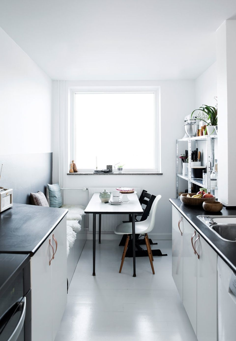 kitchen, white cabinet, black counter top, white floor, bench, black table, black chair, whtie modern chair, white shelves