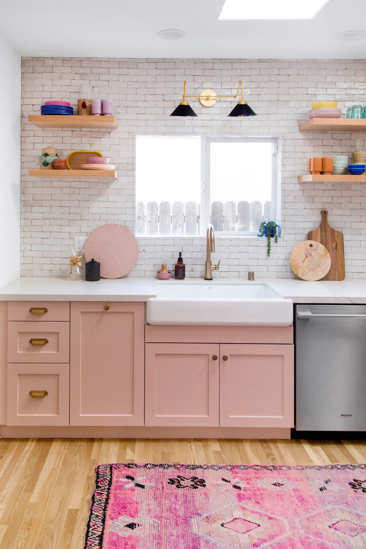 kitchen, wooden floor, pink bottom cabinet, white exposed wall, wooden floating shelves, black scones, white counter top