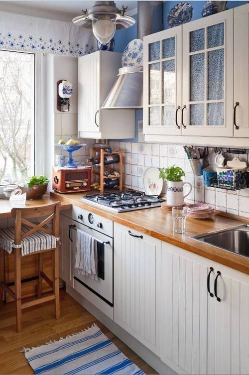 kitchen, wooden floor, white backsplash, white wooden cabinet with wooden counter top, white wooden top cabinet, wooden table, wooden chair