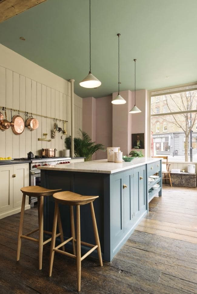 kitchen, wooden floor, white wooden wall, white wooden cabinet, green wooden island with white top, wooden stools, white pendant