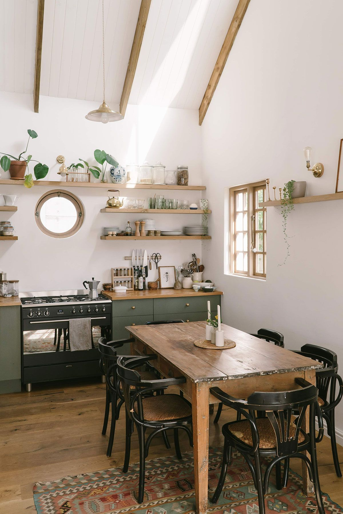 kitchen, wooden floor, wooden dining set, black wooden chairs, white wall, wooden open shelves, green bottom cabinet, wooden counter top, window