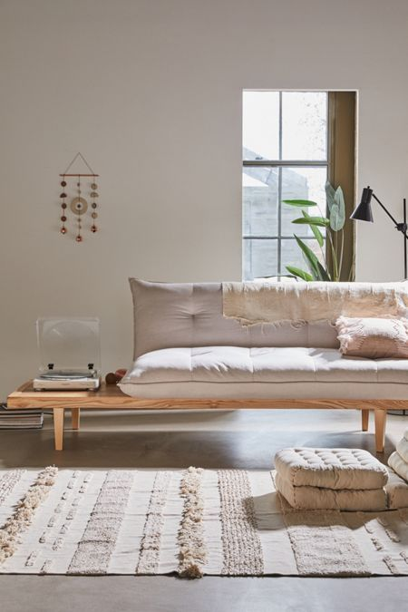 living room, concrete floor, wooden sofa, white cushion, white patterned rug