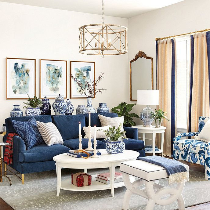 living room, grey floor, white wall, dark blue sofa, white coffee table, white ottoman, golden pendant