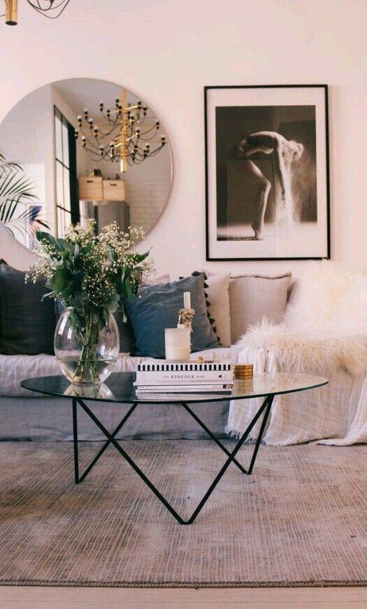 living room, grey rug, white wall, round mirror, round coffee table, grey sofa