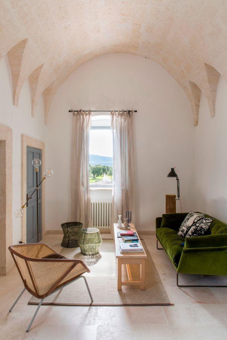 living room, off white floor tiles, white wall, green velvet sofa, long wooden coffee table, rattan chair, rattan tug, cream curtain, glass bulbs floor lamp