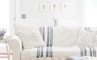 living room, white marble floor, white wall, white sofa, white blanket, brown tufted bench, white wainscoting, side tabl