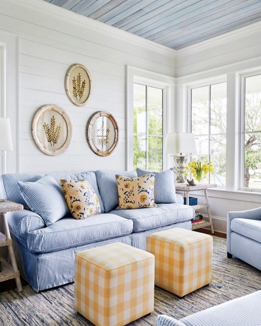 living room, white woode planks, blue wooden ceiling, white framed window, white side table, white table lamp, blue sofa, yellow ottoman