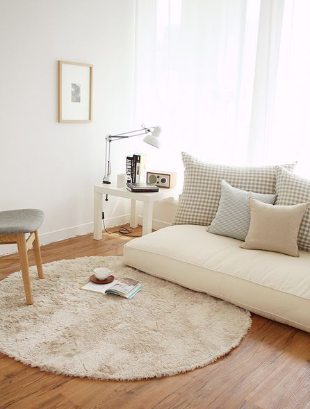 living room, wooden floor, brown round rug, white floor seating, pillows, white side table