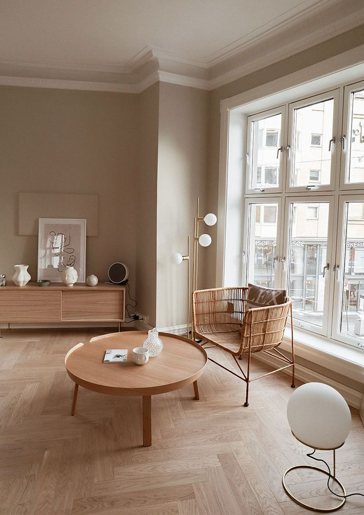 living room, wooden floor, cream wall, wooden cabinet, wooden round tray coffee table, rattan chair, white floor lamp