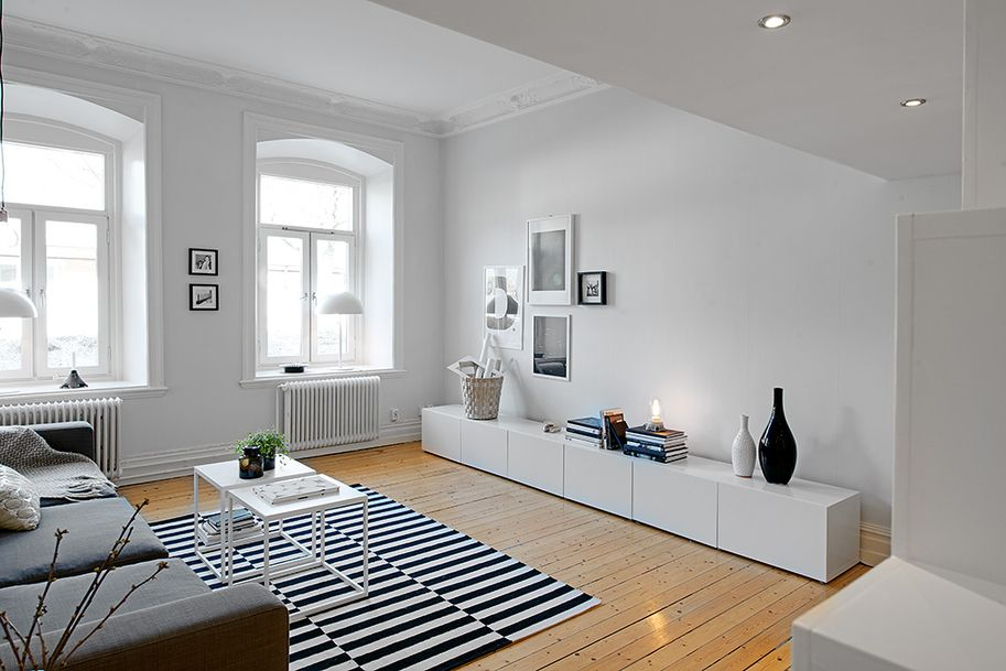 living room, wooden floor, white cabinet, grey sofa, black white striped rug, acrylic coffee table
