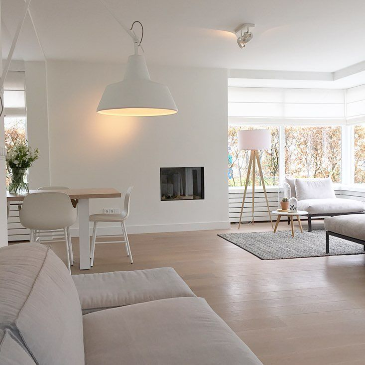 living room, wooden floor, white sofa, white chairs, white floor lamp, white pendant, wooden table, white chairs