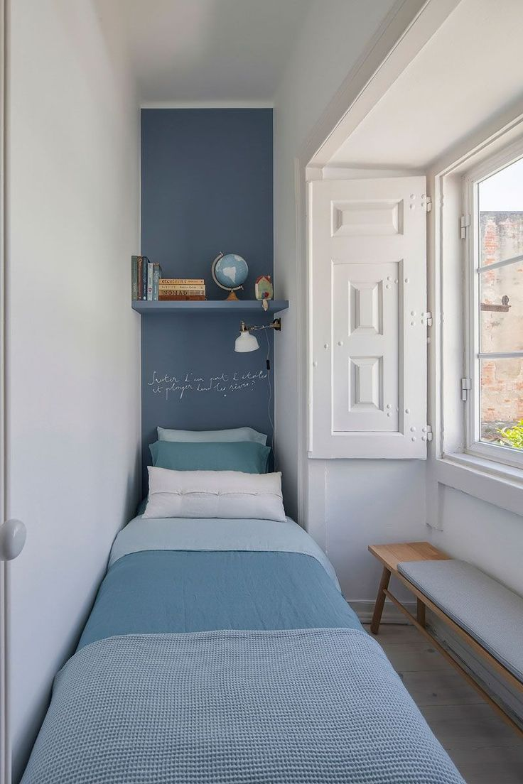 long bedroom, wooden floor, white wall, blue floating shelves, white wooden window, blue bed