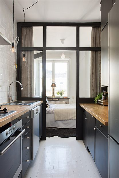 narrow and small kitchen, white wooden floor, black cabinet, white subway wall, pendants, wooden counter to
