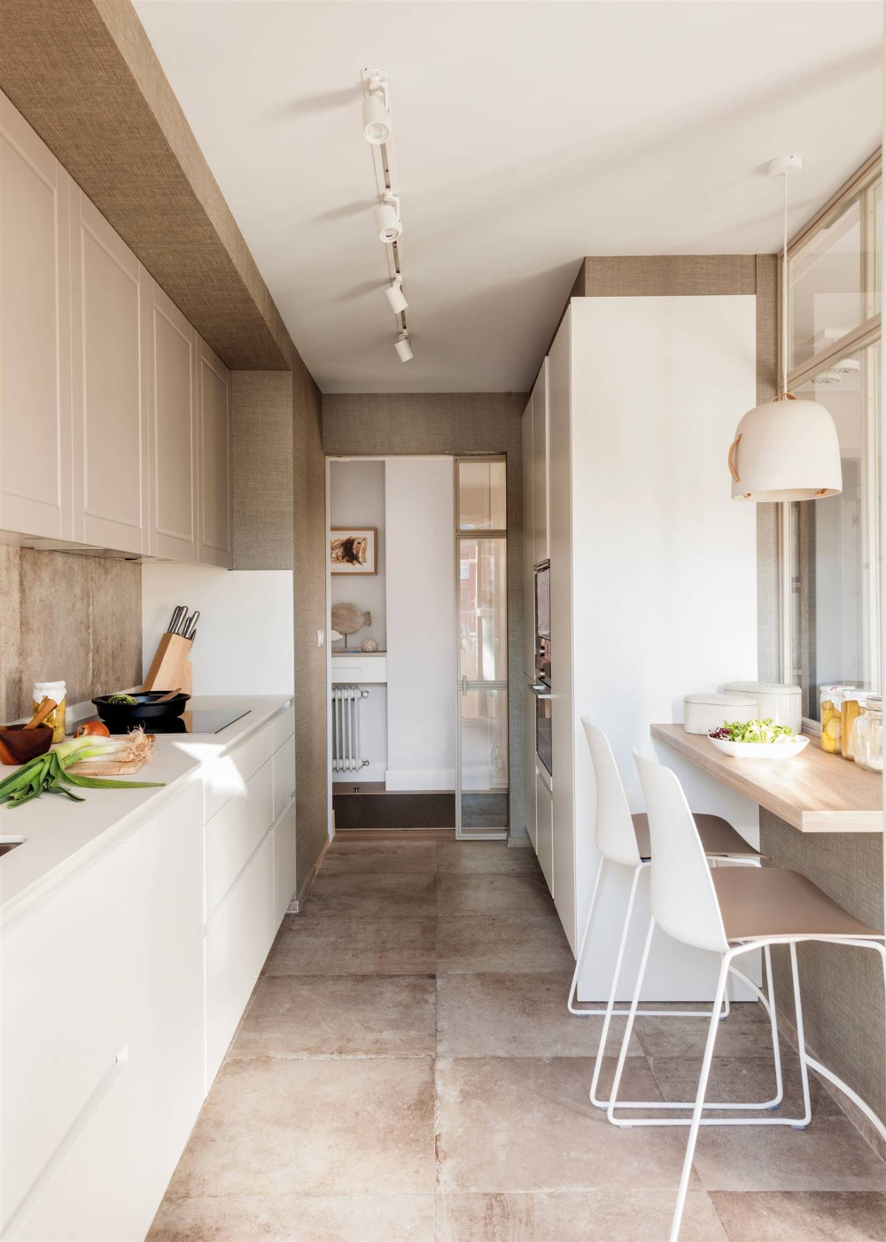 narrow kitchen, brown floor, white bottom cabinet, brown backsplash, brown top cabinet, white cabinet, wooden floating table, white chairs, white pendant