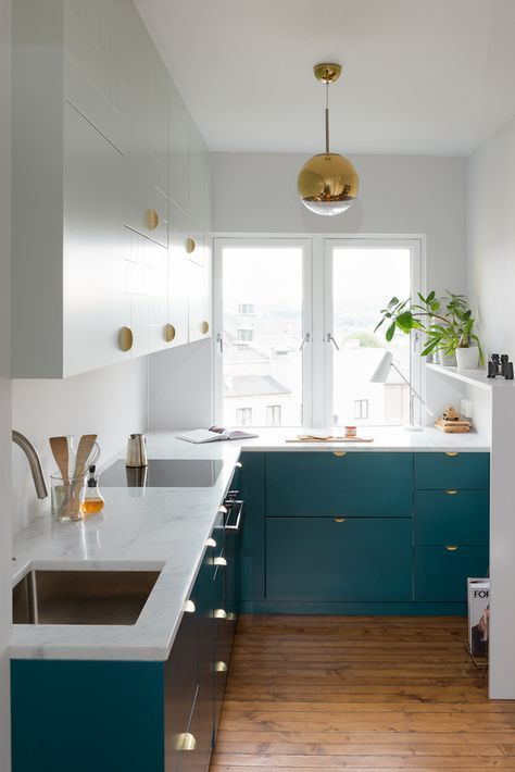 narrow kitchen, wooden floor, green cabinet, white wall, white cabinet, glossy pendant, white marble counter top