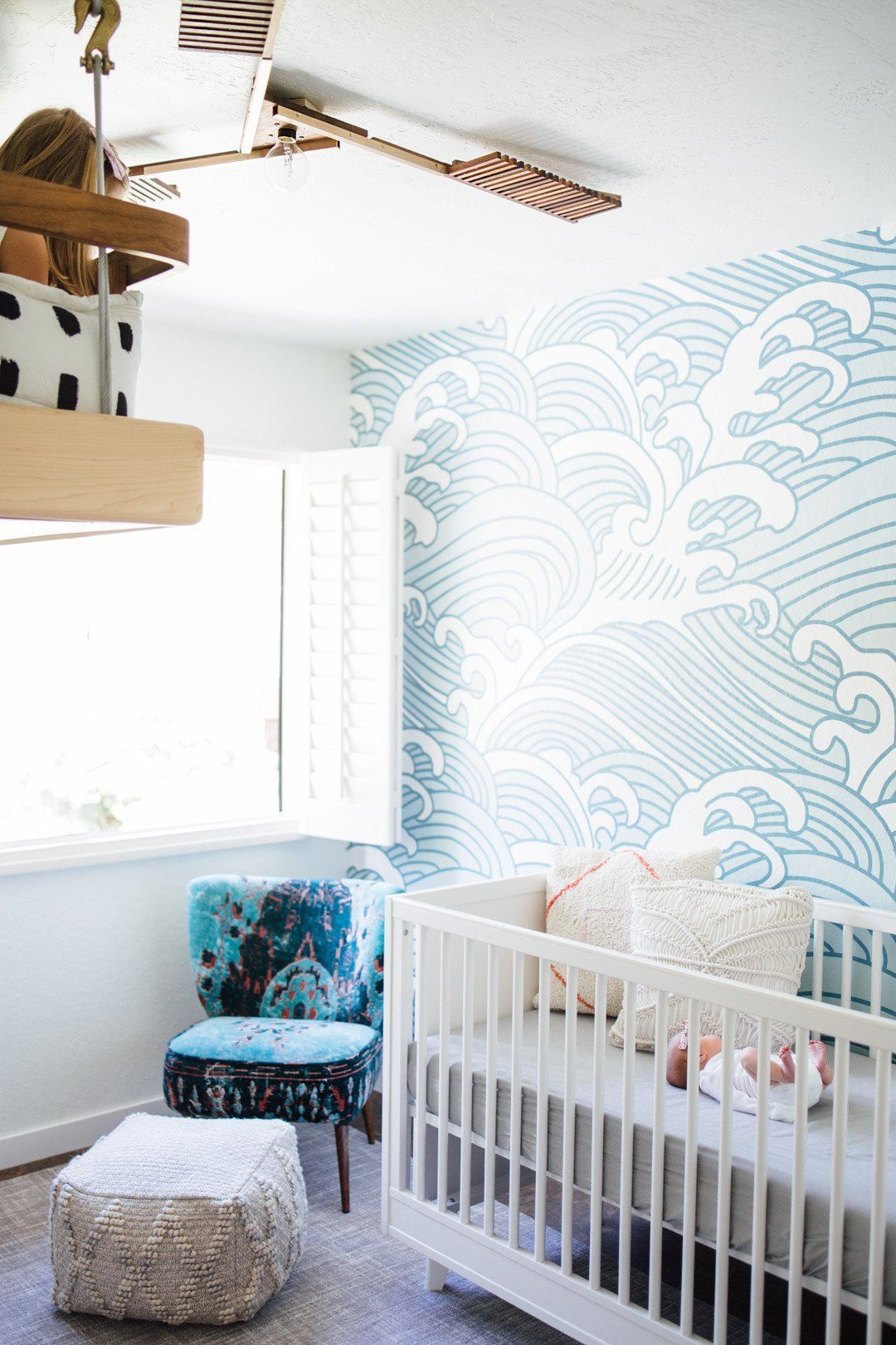 nurser, wooden floor, white rug, white wall, patterned wall, white crib, wooden floating shelves
