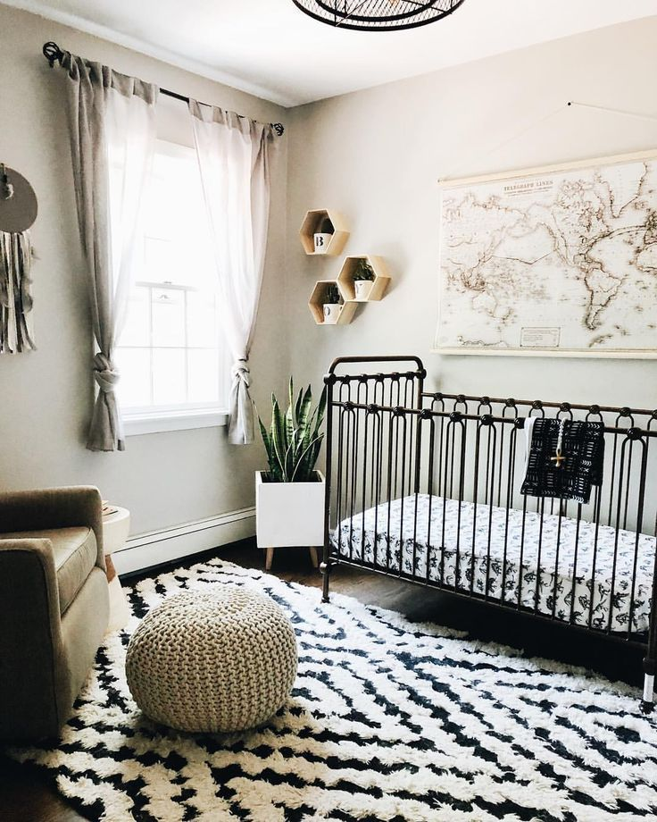 nursery, black wooden floor, white wall, brown chair, black metal crib, woven ottoman