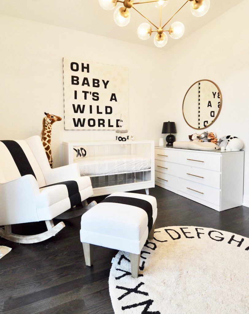nursery, black wooden floor, white wall, white cabinet, white rocking chair, white ottoman, white crib, white round rug